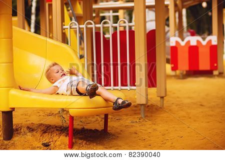 Little Boy Slides Down The Slide