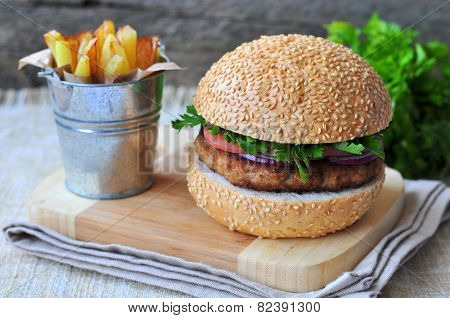Closeup of home made burgers with the fried potato on wooden and linen background