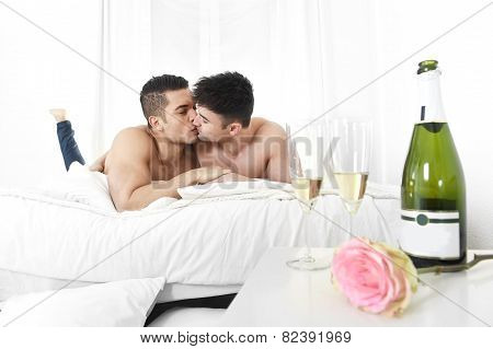 Young Gay Men Couple Kissing On Bed With Rose After Champagne Toast Celebrating Valentines Day In Ho
