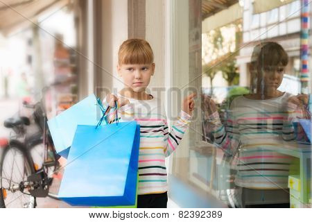 Sad Little  Girl Pointing To Shop Window
