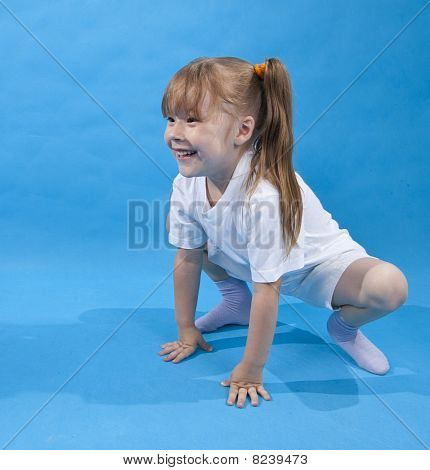 Small Girl Is Posing As Frog On Blue