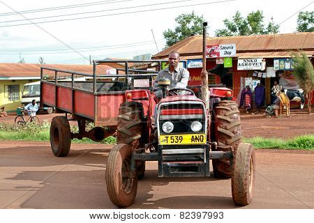 African farmers from rural Tanzania, driving a tractor-trailer.