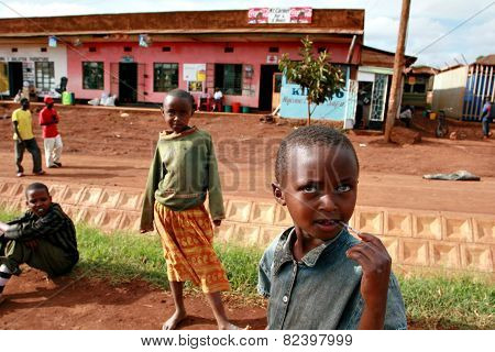 Rural African Children Sit Back In The Village Street.