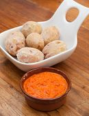 image of potato-field  - portion of canarian potatoes (papas arrugadas) with red mojo sauce on a wooden table [[** Note: Shallow depth of field] ** Note: Soft Focus at 100%, best at smaller sizes - JPG