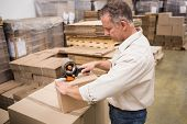 stock photo of warehouse  - Warehouse worker preparing a shipment in a large warehouse - JPG