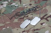 stock photo of camouflage  - us army camouflaged uniform with blank dog tags - JPG