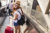 stock photo of escalator  - Young cute girl with the red suitcase standing on the escalator - JPG