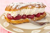 picture of eclairs  - Bright light from behind creamy perfection of raspberry eclair on dessert plate with fork - JPG