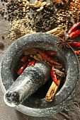 stock photo of garam masala  - Granite mortar and pestle with spices ready for grinding - JPG