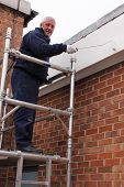 picture of scaffold  - A painter working from a scaffold tower - JPG