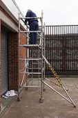 image of scaffold  - A painter working from a scaffold tower - JPG