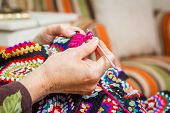 stock photo of quilt  - Hands of senior woman knitting a vintage wool quilt with colorful patches - JPG