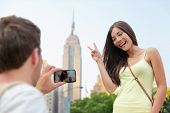 stock photo of empire state building  - NYC asian chinese tourist girl posing at Empire State Building doing the v hand sign - JPG