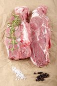 stock photo of cold-shoulder  - lamb shoulder chops with coarse salt pepper and rosemary on brown kitchen paper - JPG