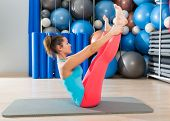 stock photo of pilates  - Pilates Open Leg Rocker exercise on mat woman with balls background gym - JPG