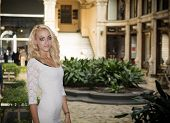 stock photo of posh  - Elegant pretty blonde young woman standing in white dress in posh city setting in Europe - JPG