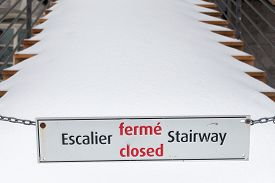 stock photo of stairway  - Sign of closed stairway in french and English with a stairway in background full of snow - JPG