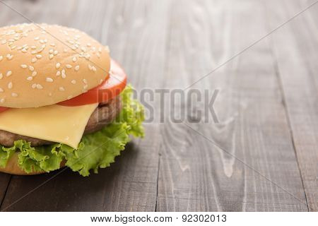 Half Juicy Cheeseburger On The Wooden Background.