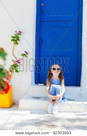 Charming little girl at typical greek traditional village with white houses and colorful doors on Mykonos Island, Greece, Europe