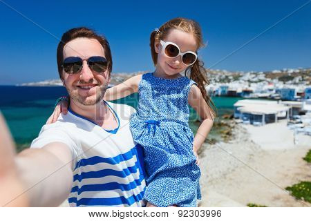 Happy family father and his adorable little daughter on vacation taking selfie at Little Venice area on Mykonos island, Greece