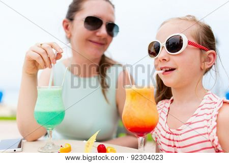 Happy mother and her adorable little daughter at outdoors cafe drinking tropical juice