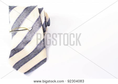 Striped tie roll with tie clip isolated on white background