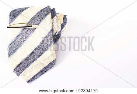 striped necktie roll with tie clip isolated on white