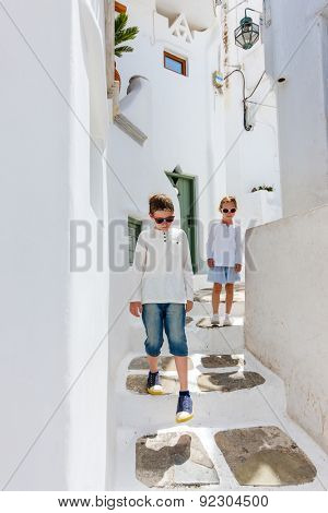 Kids at typical greek traditional village with white walls and colorful doors, windows and balconies on Mykonos Island, Greece, Europe