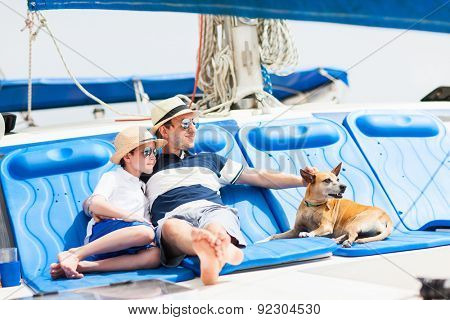 Father, son and their pet dog sailing on a luxury yacht or catamaran boat