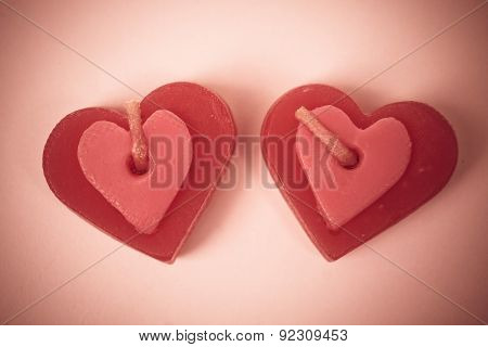 two red scented candles with shapes of a heart on red background. Valentine's Day