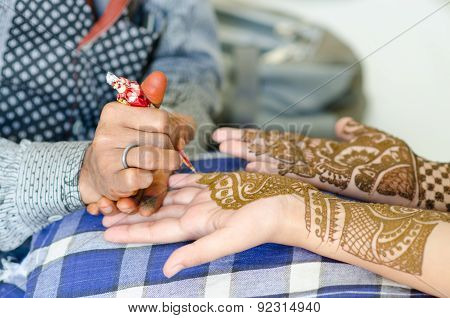 mage detail of henna being applied to hand.