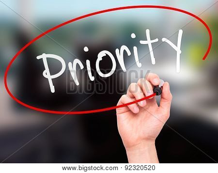 Man Hand writing Priority with marker on transparent wipe board.
