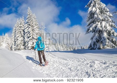 Young woman with dawn jacket in winter mountains