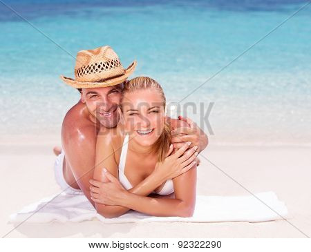 Happy couple lying down on beautiful sandy shore, having fun outdoors, spending honeymoon vacation on beach resort, love and romance concept
