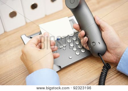 Businessman Is Reading Telephone Number From Business Card To Make A Call