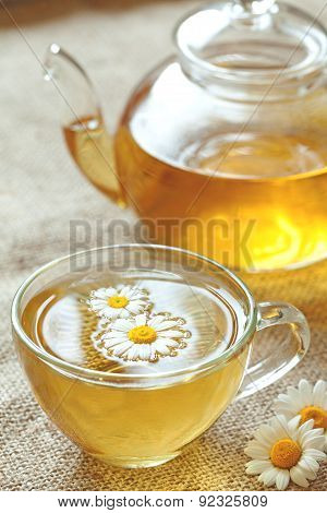 Cup of camomile tea with chamomile flowers and teapot. Chamomiles on background.
