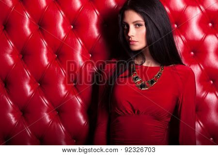 young woman in red dress standing near wall