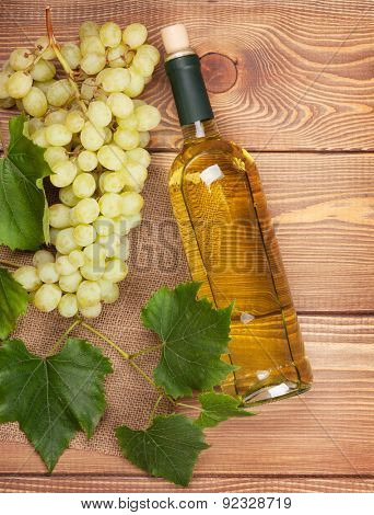 White wine bottle and bunch of white grapes on wooden table background