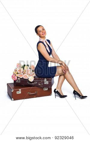 Beautiful Young Brunette Woman In A Short Dress Sitting On A Vintage Suitcase, Lie Near The Pink Ros