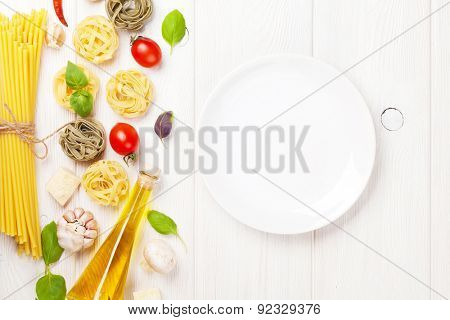 Italian food cooking ingredients and empty plate. Pasta, tomatoes, basil. Top view with copy space