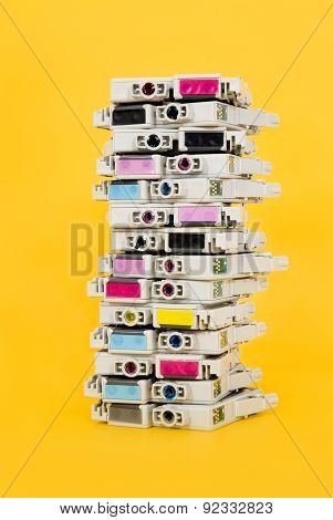Ink cartridges exhausted stacked on yellow background