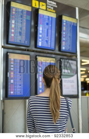 Girl watching flight information board in airport terminal. Passenger checking the time of the flights on the arrival departure board.