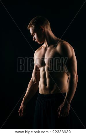 muscular young man showing his biceps isolated on black backgro