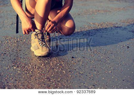 young asian woman hiker tying shoelace on sunrise beach