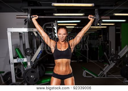 beautiful sports fitness girl with a barbell in the gym, crouches