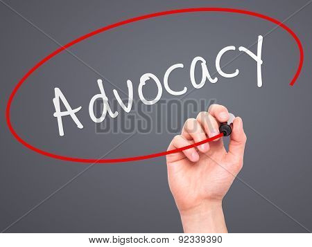 Man Hand writing Advocacy with marker on transparent wipe board.