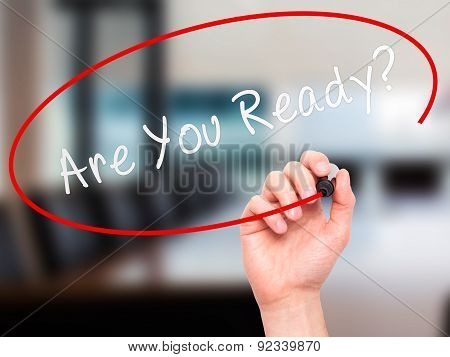 Man Hand writing Are You Ready with marker on transparent wipe board.