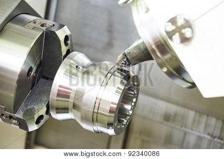 modern metal working machine with cutter tool during metal detail turning at factory