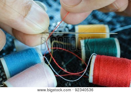 Closeup Hand Pulling Thread Into Needle