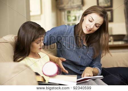 Mother Helping Daughter With Homework Sitting On Sofa At Home